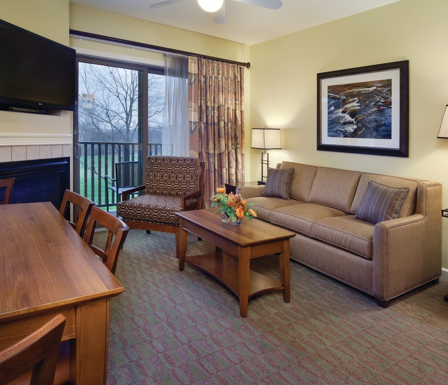 Living room with couch, accent chair, fireplace and flat screen TV in a one-bedroom villa at Lake Geneva Resort