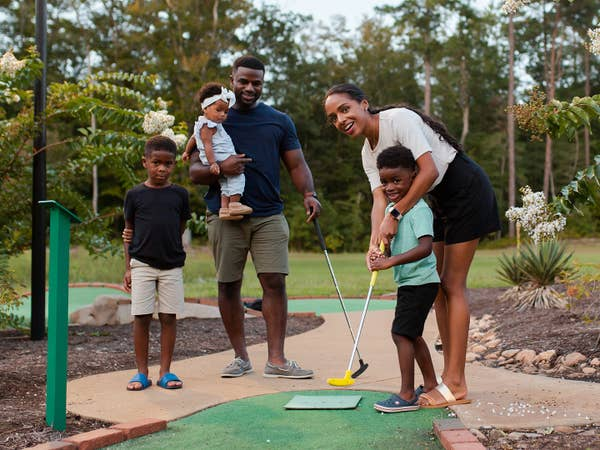 Family playing mini golf.