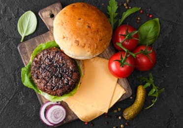 Burger preparations with bun, patty, cheese, tomatoes, pickle and onion on cutting board.