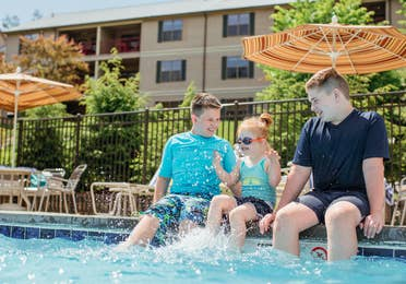 Three children sitting on edge of outdoor pool at Oak n' Spruce Resort in South Lee, Massachusetts.