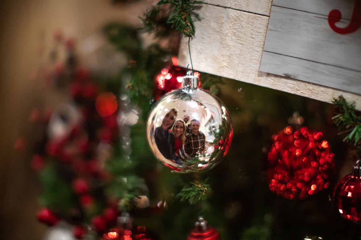 The Nall family look into a silver ornaments reflection as it hangs from a christmas tree.