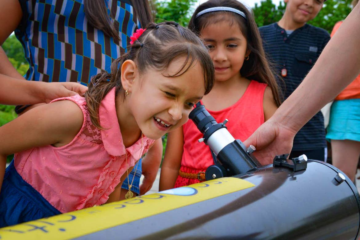 A young girl looks into a telescope as other watch.