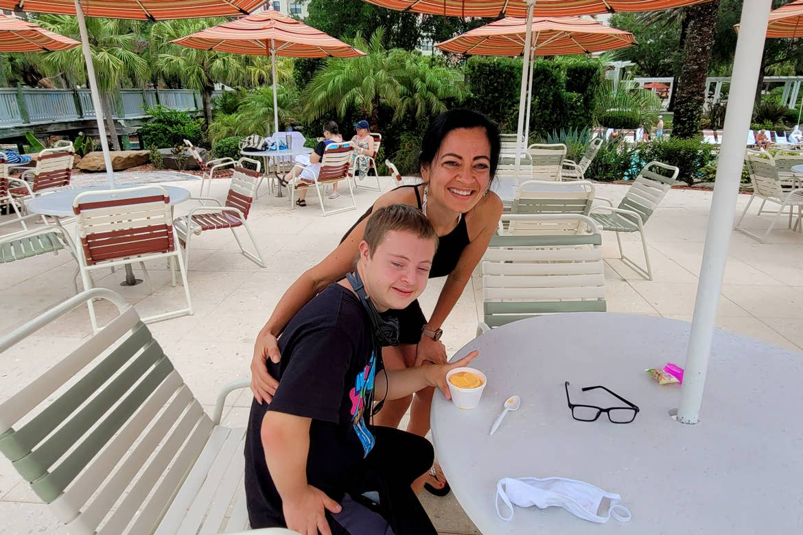 A woman (back) stands behind a young boy (front) eating a cup of ice cream.