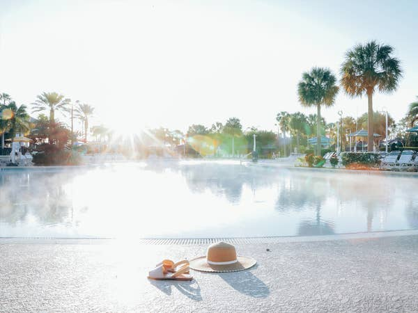 Sunhat and sandals sitting in front of pool at Orange Lake Resort near Orlando, Florida.