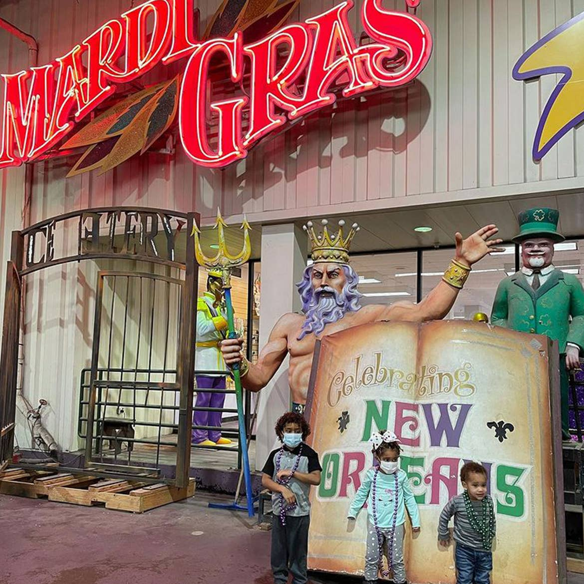 Featured Contributor, Sally Butan of @butanclan's daughter, Alissa (middle), and sons, Alex (left) and Alston (right) pose next to a giant book prop that reads, 'Celebrating New Orleans' outside of  Mardi Gras World in New Orleans, Louisiana.