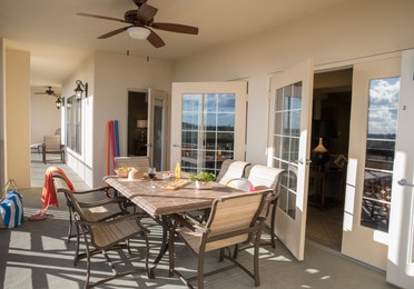 Furnished balcony with ceiling fans and a table with six chairs in a four bedroom Signature villa in River Island at Orange Lake Resort near Orlando, Florida