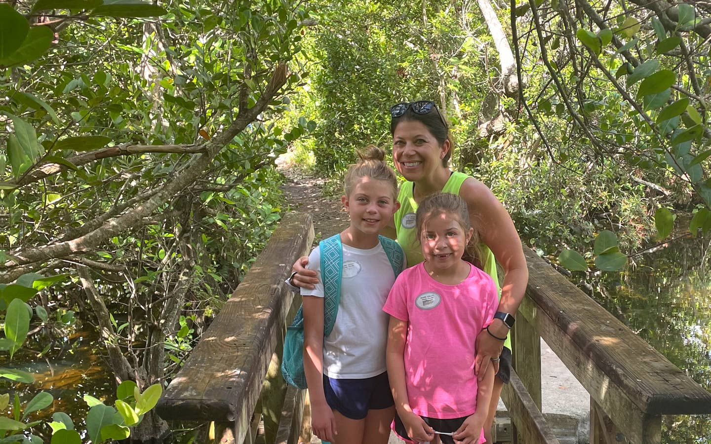 A caucasian woman (middle) poses with two young caucasian girls (front) on a wooden bridge in the Everglades.