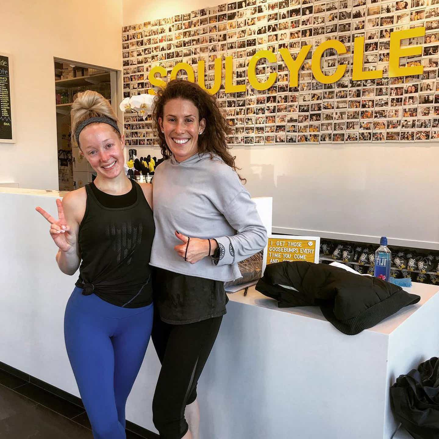 Co-author, Molly (left), wears a black tank and blue leggings while posing with a friend near a SoulCycle entrance.