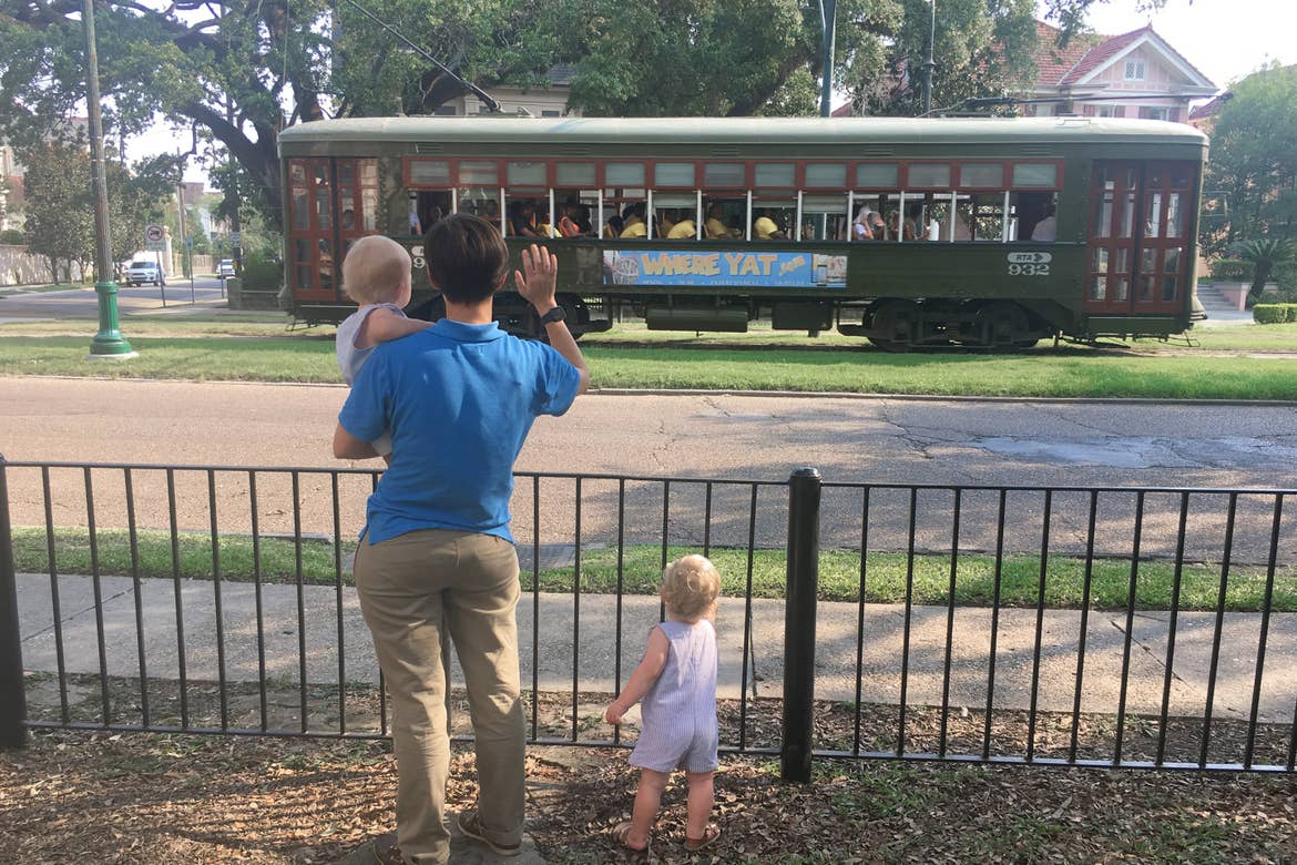 Featured Contributor, Catherine Karas' wife stands with her boys waving to the streetcar.