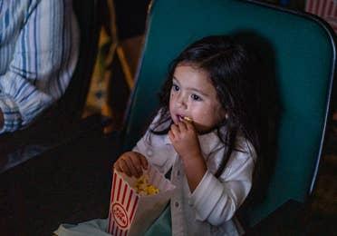 Movie theater, girl enjoying popcorn at Ozark Mountain Resort