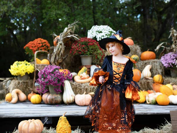 Child dressed in a witch Halloween costume standing outside by hay bales and pumpkins.