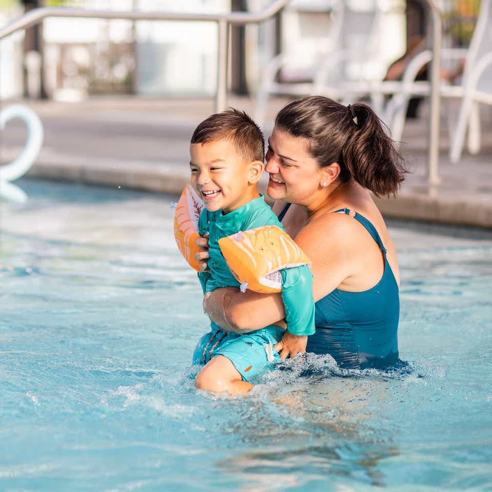 Adult holding child while laughing in resort pool at Holiday Hills Resort in Branson, Missouri.