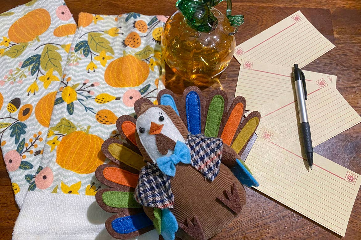 Festive towels (left) a hand-knitted turkey (middle) and recipe cards (right) are spread upon a kitchen table.