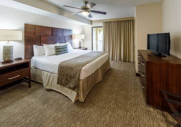 Master bedroom with king bed and flat screen TV in a two-bedroom villa at Scottsdale Resort