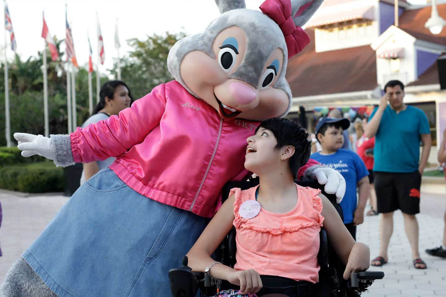 Miss Merry the Bunny (left) wears a pink coat and bow as she embraces a young villager in a wheelchair (right).