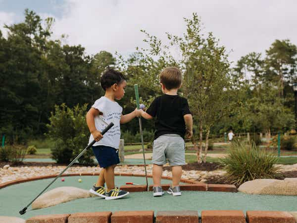 Two young children playing mini golf at Williamsburg Resort.