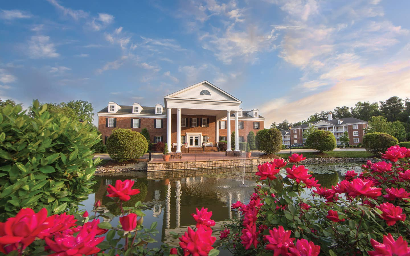 Property building surrounded by pink flowers at Williamsburg Resort in Virginia.
