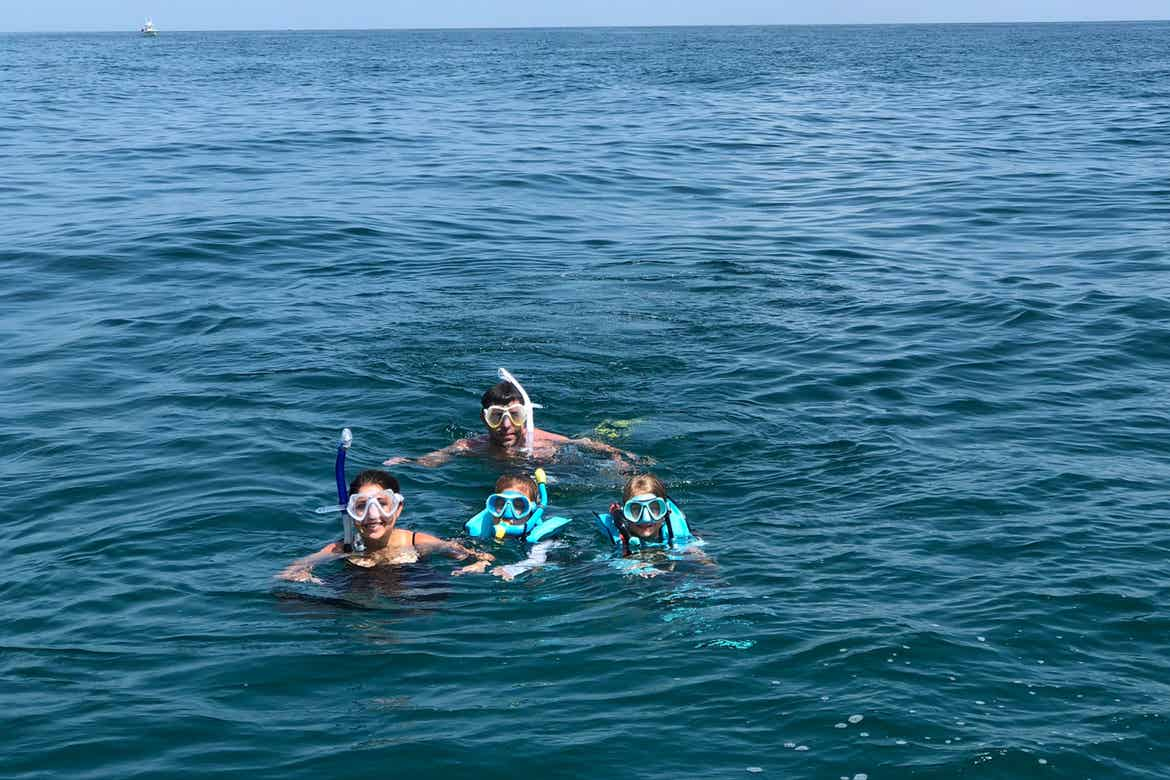 Chris Johnston (front-left), snorkels with her husband, Josh (middle-back), and two daughters, Kyler (front-middle) and Kyndall (front-right), in the ocean.