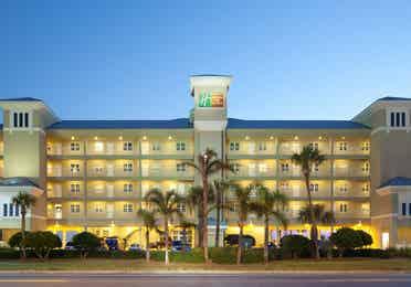 Property building and palm trees at night at Panama City Beach Resort