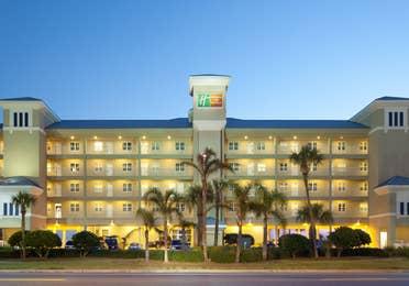 Property building and palm trees at night at Panama City Beach Resort.