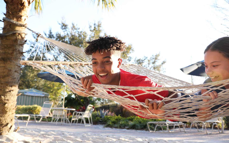 Two teens at Orange Lake Resort playing on a hammock