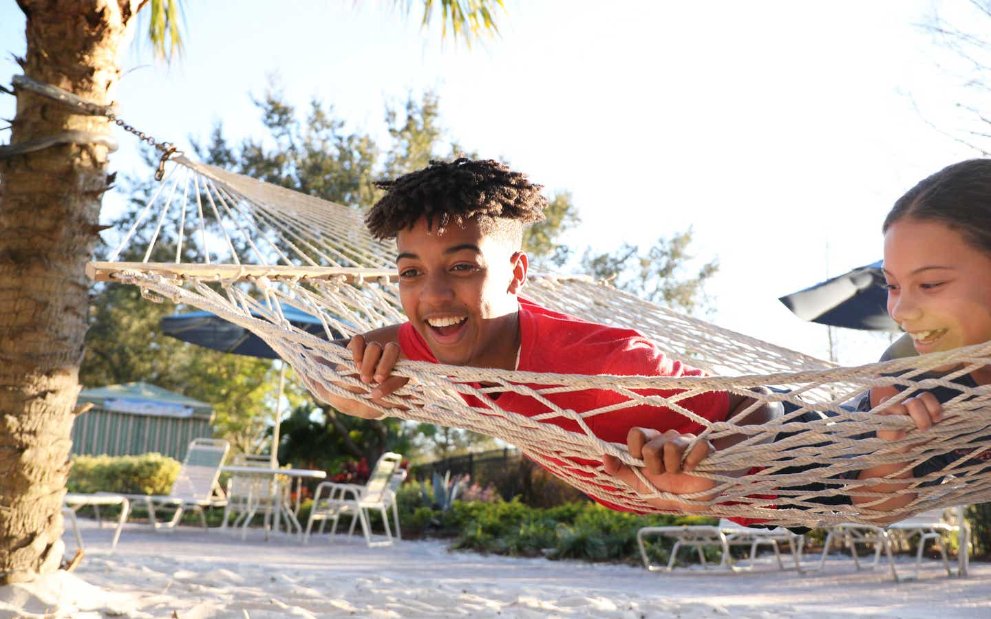 Two teens at Orange Lake Resort playing on a hammock