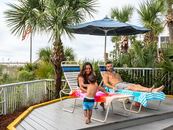 Two adults and child sitting under pool umbrella at Beach Club at South Beach Resort in Myrtle Beach, South Carolina.