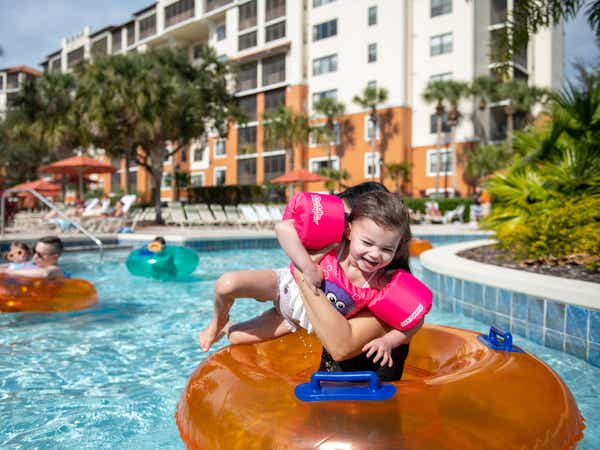 Family floating down the lazy river with inner tubes at Orange Lake Resort in Orlando, FL.