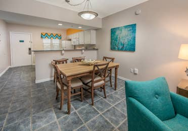 Dining room with table and five chairs in a one-bedroom villa at Panama City Beach Resort