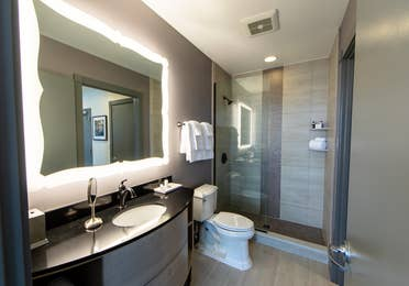 Signature Collection two bedroom villa bathroom with walk-in shower, toilet and sink with lighted mirror at New Orleans Resort in Louisiana.