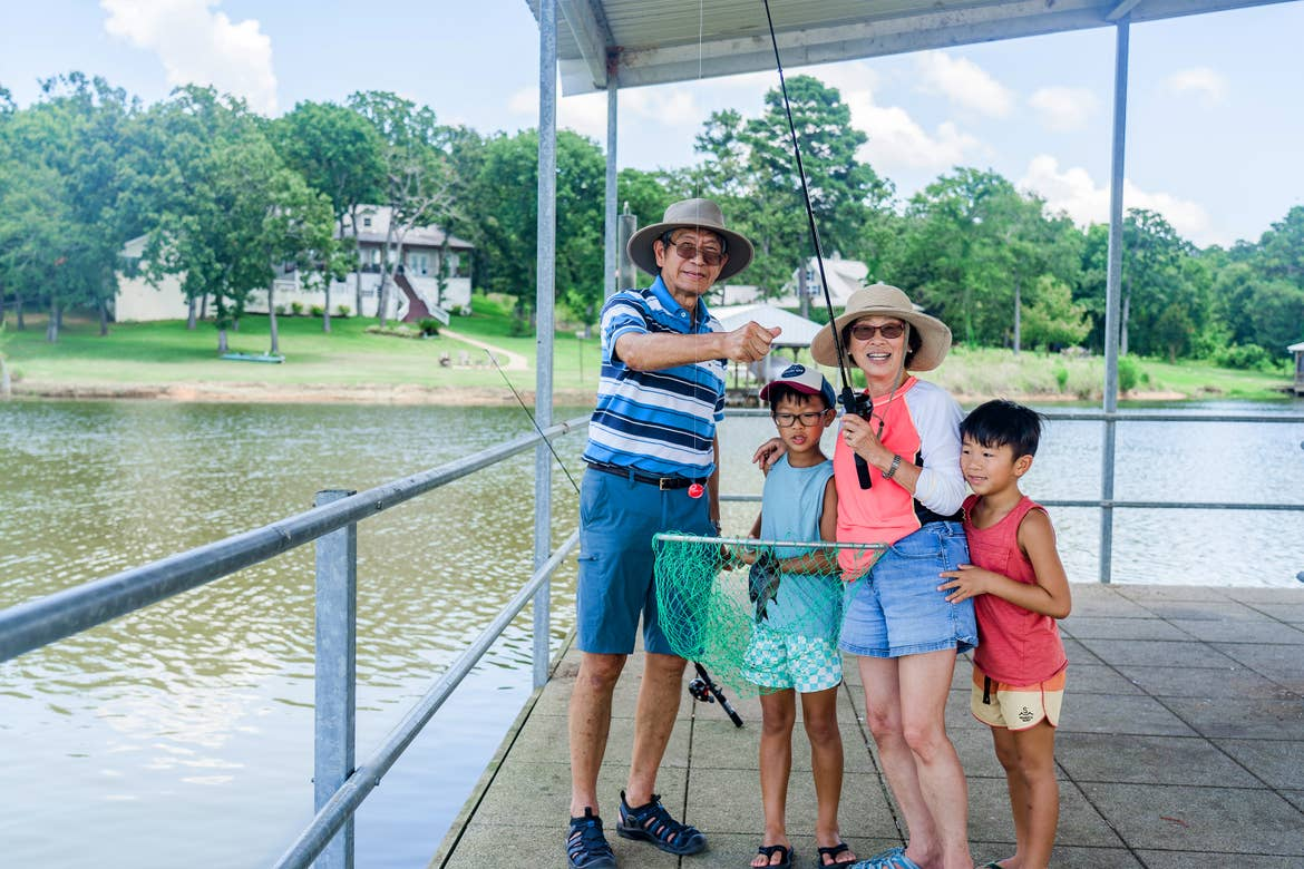 An older Asian male (left) and female (middle-right) surrounded by two young male boys wear  sunglasses and various hats while holding up fishing gear and their catch.