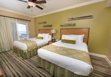 Guest bedroom with two beds and access to the balcony in a Signature two-bedroom villa at Galveston Beach Resort