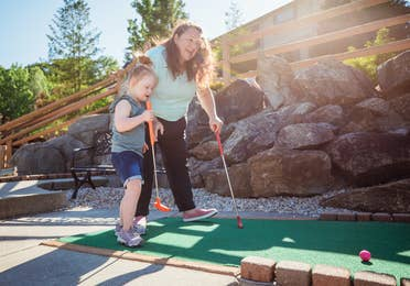 Mother and daughter playing mini golf outdoors at Oak n' Spruce Resort in South Lee, Massachusetts.
