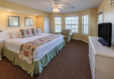 Master bedroom with king bed, flat screen TV, and seating area in a presidential two bedroom villa at Piney Shores Resort in Conroe, Texas