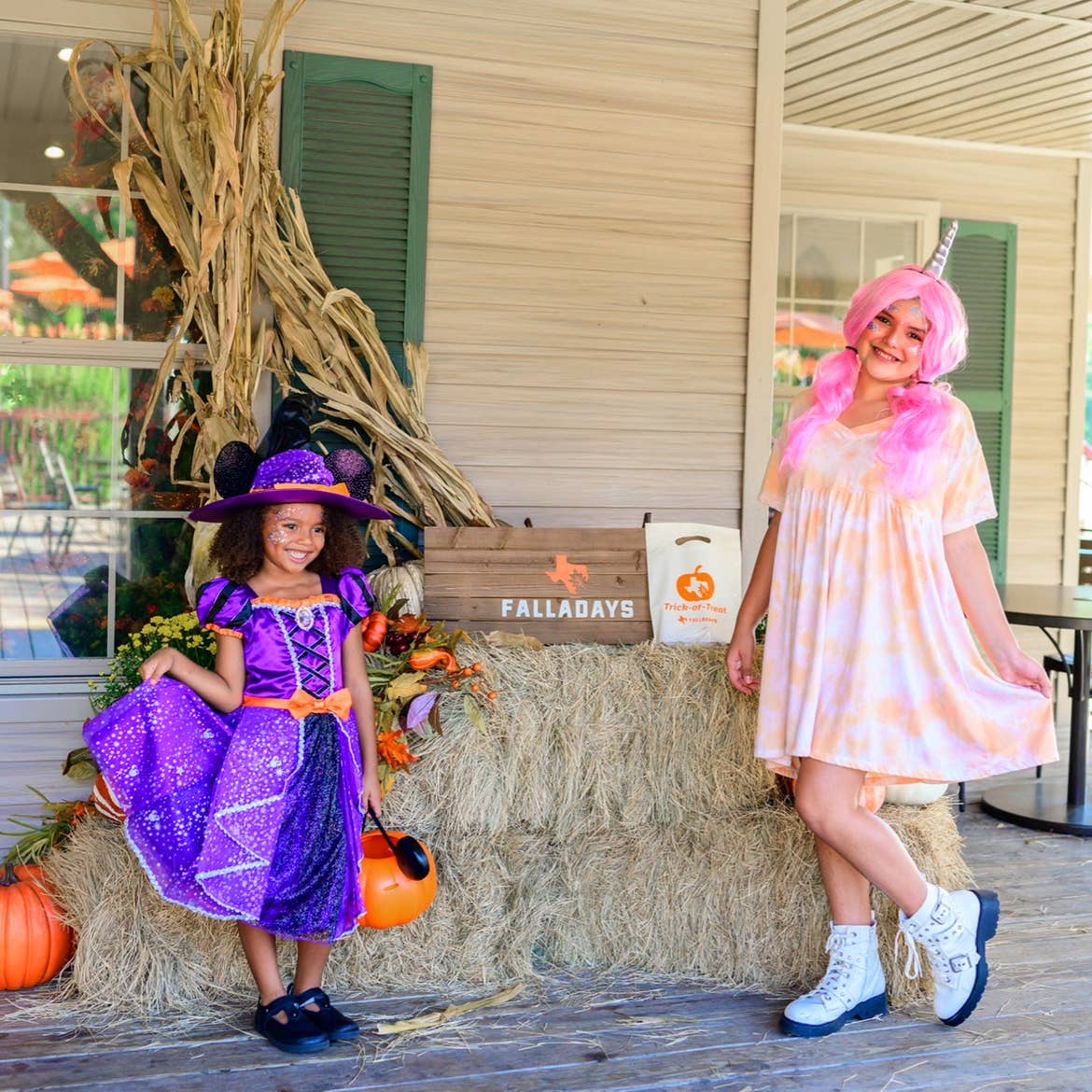Two girls wear halloween costumes near a hay bail outdoors.