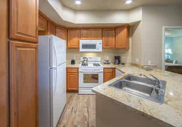 Kitchen with refrigerator, stove and microwave in an upgraded one-bedroom villa at David Walley's Resort in Genoa, Nevada