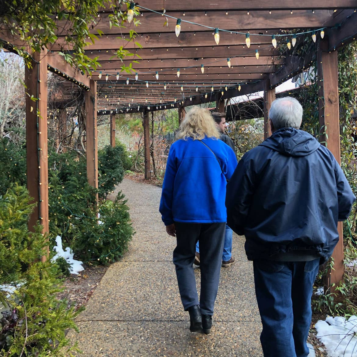 Author, Jenn C. Harmon's mother (left) and father (right) walk under the trellis of the gardens at the Biltmore Estate property.v