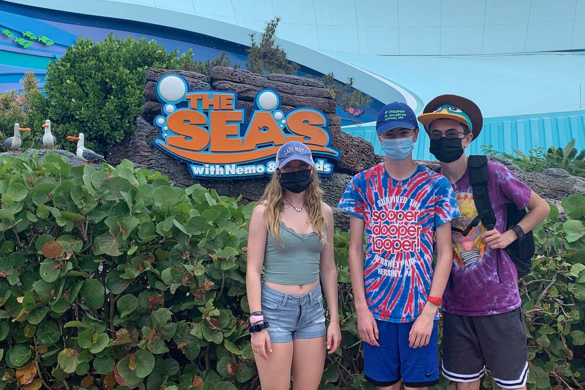 A teenage girl (left) and two boys (right) wear Disney hats and safety masks near the marquee for 'The Seas' in EPCOT at Walt Disney World Resort.