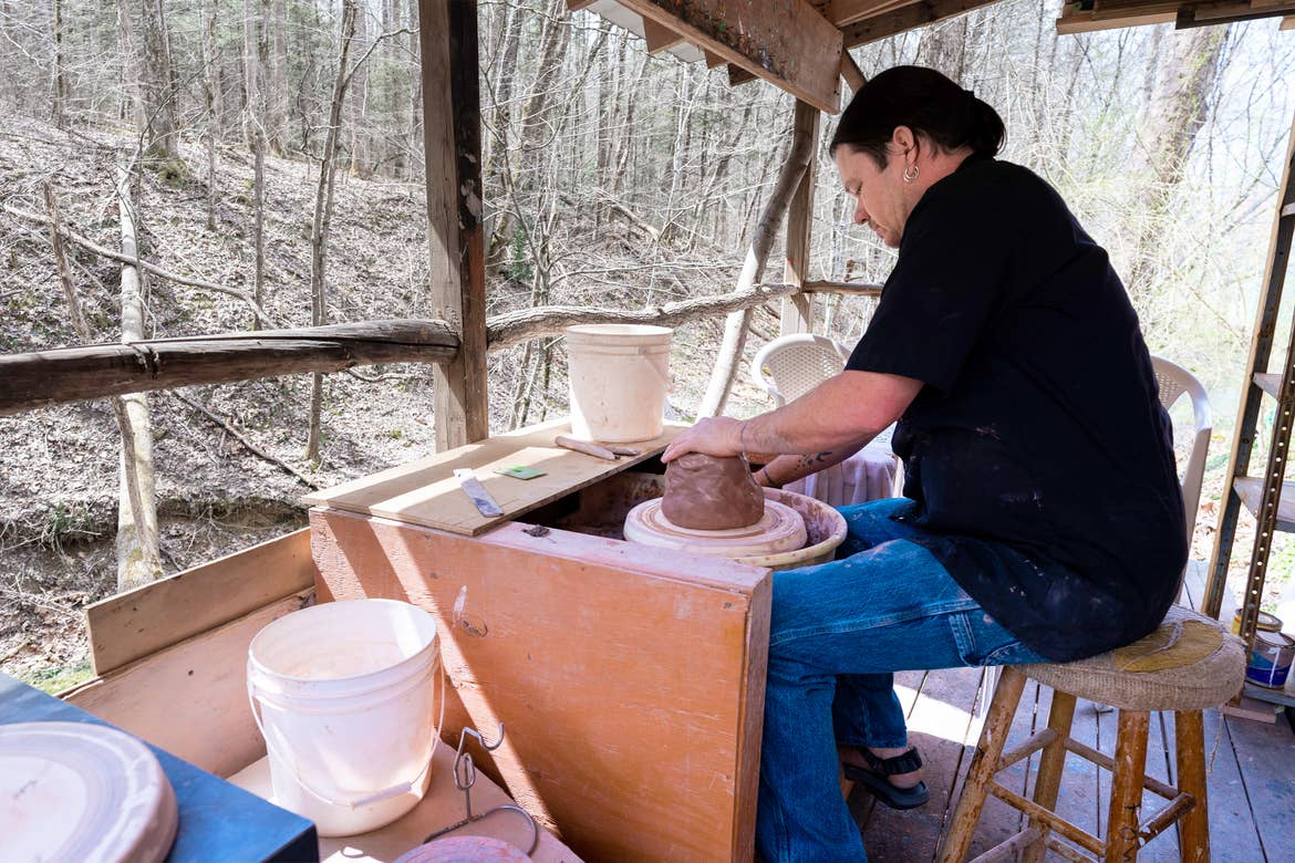 A man works with clay pottery outdoors while wearing a black shirt and jeans at Fowler's Clay Works.
