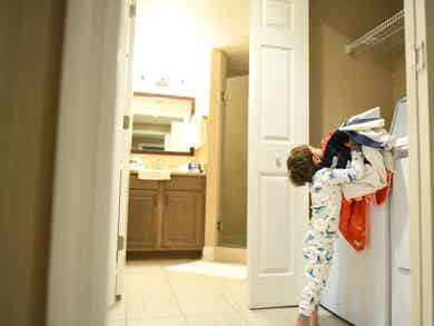 Kid trying to put laundry in a washing machine.