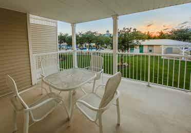 Furnished balcony with a table and four chairs in a one-bedroom Presidential villa at Hill Country Resort in Canyon Lake, Texas