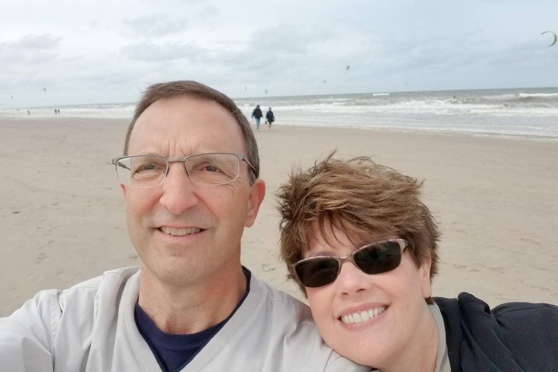 A caucasian man (left) wears a light grey crewneck sweater next to a caucasian woman (right) on a beach in Zandvoort, Netherlands.