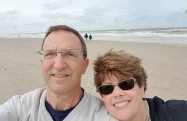A man (left) wears a light grey crewneck sweater next to a woman (right) on a beach in Zandvoort, Netherlands.