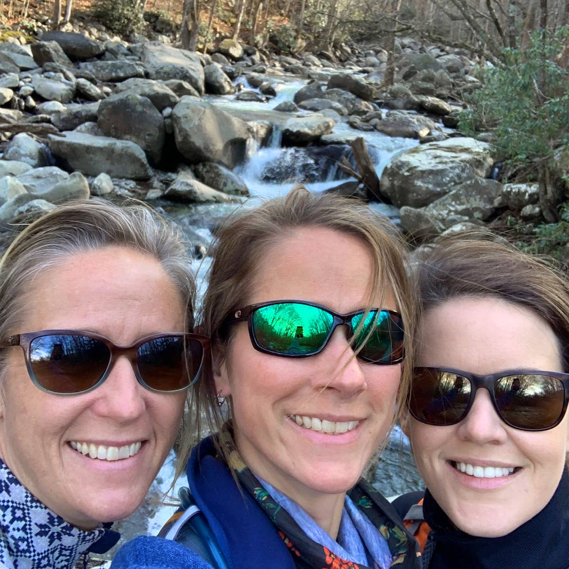 Featured Contributor, Jennifer C. Harmon (right) and her two girlfriends wear sunglasses in front of a waterfall.