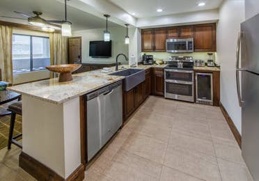 Full kitchen with stainless steel oven, microwave, fridge, dishwasher, and sink in a signature one-bedroom villa at Scottsdale Resort