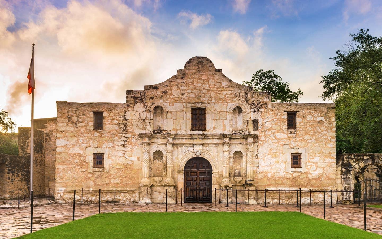 The Alamo in San Antonio, Texas underneath a blue, cloudy sunset sky.