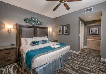 Bedroom with a king sized bed and attached bathroom in a three-bedroom villa at Sunset Cove Resort in Marco Island, Florida