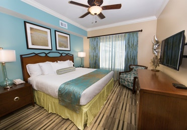 Master bedroom with large window, seating area, and flat screen TV in a Signature two-bedroom villa at Galveston Beach Resort
