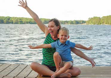 Author, Sarah Conroy, and son, Logan, sit on a lake pier mimicking an airplane with their arms.