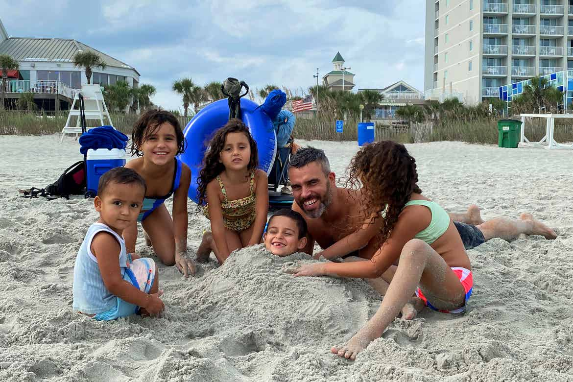 Author, Brenda Rivera Sterns' family plays in the sand on the beach in front of our South Beach Resort in Myrtle Beach, South Carolina.